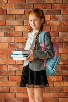 Leuk schoolmeisje met schooltas houdt schoolboeken