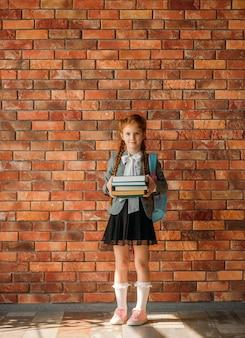 Leuk schoolmeisje met schooltas houdt stapel handboeken