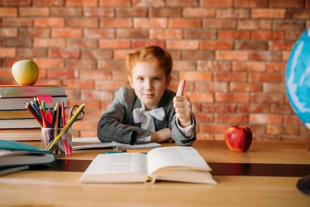 Leuk schoolmeisje zit aan de tafel en duimen opdagen