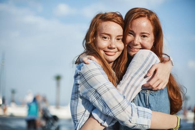Leuk schot van twee mooie vriendinnen met rood haar en sproeten, knuffelen op straat en breed glimlachend, zorg en liefde uitdrukken. levensstijl en relatie concept