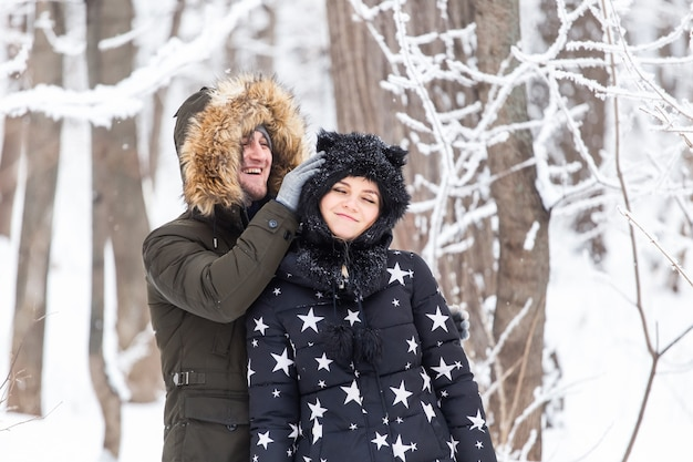 Leuk seizoen en vrijetijdsconcept liefdespaar speelt winterhout op sneeuw