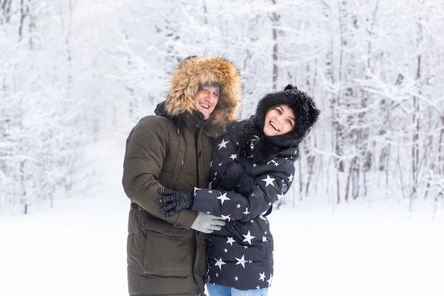 Leuk seizoen en vrijetijdsconcept, paar dat op sneeuw speelt
