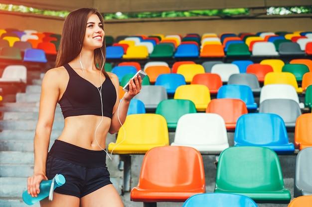 Leuk sportief meisje met telefoon en fles openlucht