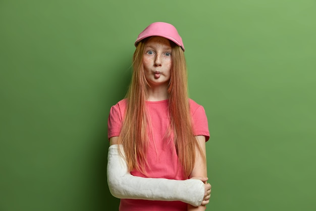 Leuk sproeterig meisje maakt grappig gezicht, vislippen, heeft lang steil rood haar, draagt een roze pet en t-shirt, gebroken arm in het gips, staat tegen een groene muur. kinderen, gezichtsuitdrukkingen, ongelukken