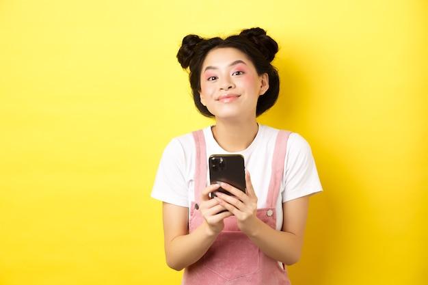 Leuk stijlvol aziatisch meisje met behulp van mobiele telefoon, glamour roze make-up en zomerkleding dragen, staande op geel.