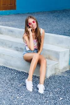 Leuk stijlvol meisje met blauwe achtergrond zit op de veranda en luistert naar muziek op oortelefoons op smartphone.