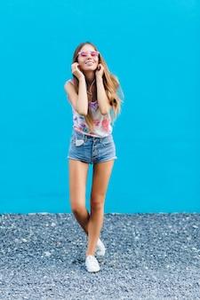 Leuk stijlvol meisje op blauwe achtergrond staat en luistert naar muziek op oortelefoons op smartphone.