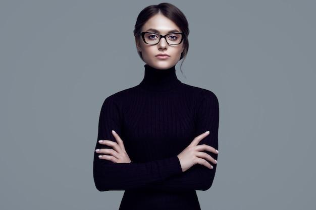 Leuk studentenmeisje dat zwarte colsweater en modieuze oogglazen draagt