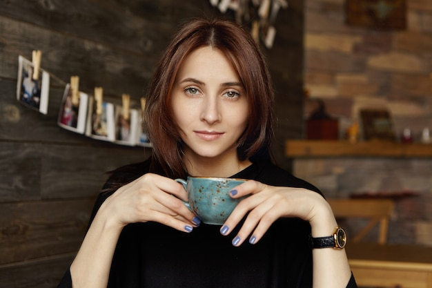 Leuk studentenmeisje die met blauwe spijkers mok houden, die van verse cappuccino genieten bij koffiewinkel