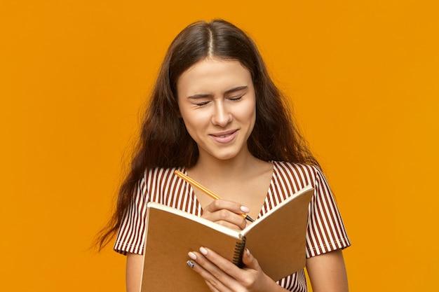 Leuk studentenmeisje met losse lange haren die ogen gesloten houden, lachend om iets grappigs