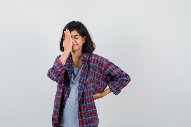 Leuk tienermeisje dat de hand op het oog houdt in een geruit overhemd en er somber uitziet, vooraanzicht.