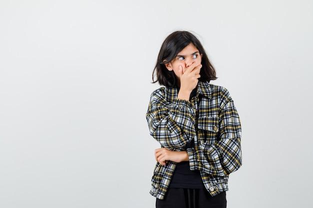 Leuk tienermeisje dat hand op mond houdt, omhoog kijkt in geruit overhemd en angstig kijkt. vooraanzicht.
