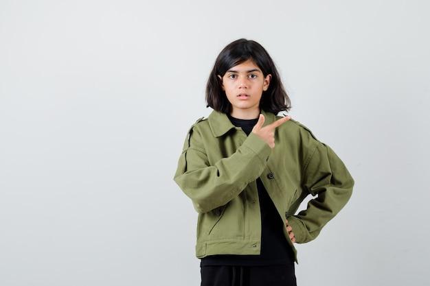 Leuk tienermeisje dat naar de rechterbovenhoek wijst in een legergroen jasje en verbaasd kijkt. vooraanzicht.