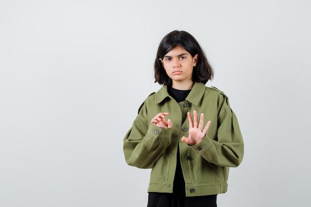 Leuk tienermeisje dat stopgebaar in legergroen jasje toont en er bang uitziet, vooraanzicht.