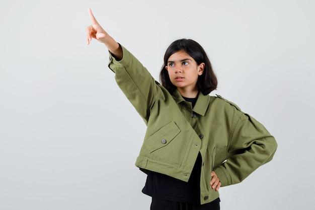 Leuk tienermeisje dat wegwijst in een legergroen jasje en er gefocust uitziet, vooraanzicht.