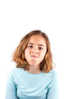 Leuk tienermeisje die met grappige gezichtsuitdrukking aan camera kijken,