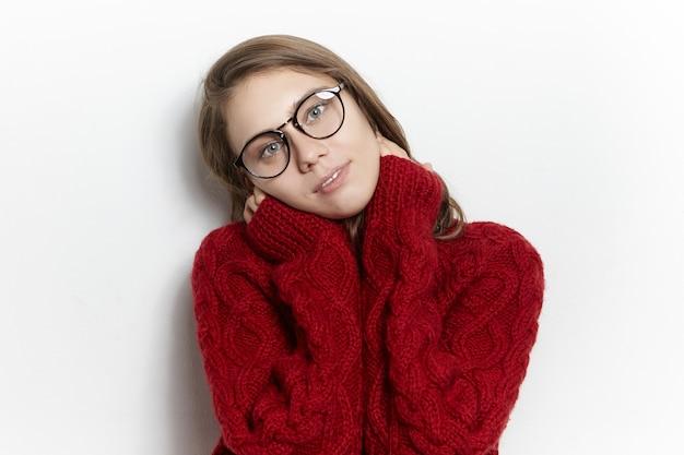 Leuk tienermeisje in brillen en gezellige pullover poseren binnenshuis. charmante jonge europese vrouw in goed humeur ontspannen op koude dag, warme gebreide coltrui en transparante glazen dragen