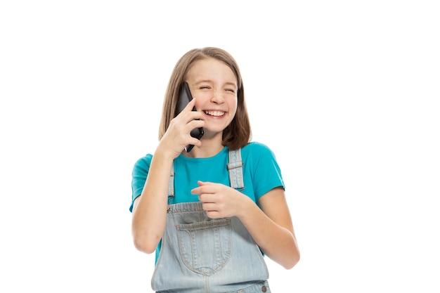 Leuk tienermeisje in denimoverall die op de telefoon en het lachen spreken. geã¯soleerd op een witte achtergrond.