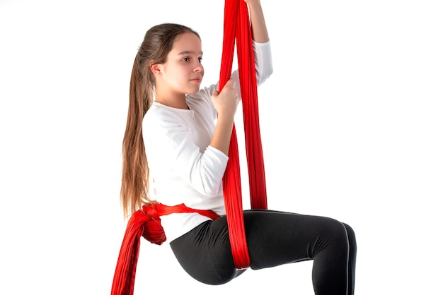 Leuk tienermeisje in een witte sweater en zwarte beenkappen die sportenacrobatiek doen die een rood luchtlint op een wit gebruiken