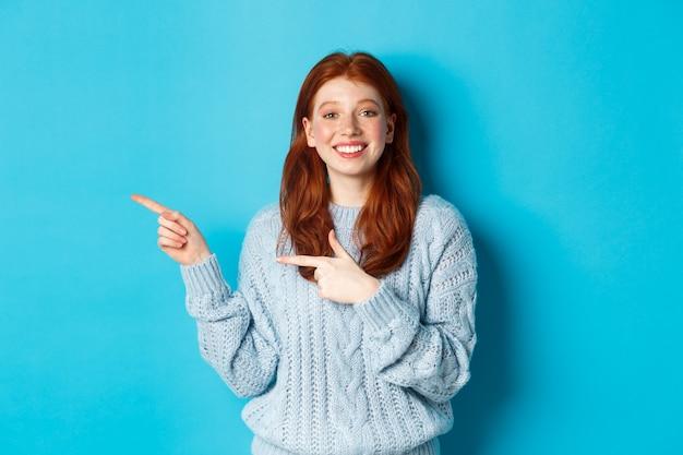 Leuk tienermeisje met rood haar en sproeten, wijzende vingers links op logo en glimlachen, reclame tonen, staande over blauwe achtergrond.