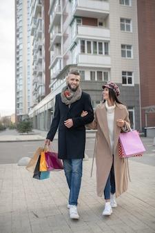 Leuk trendy stel dat samen gaat winkelen terwijl ze de moderne mode volgen