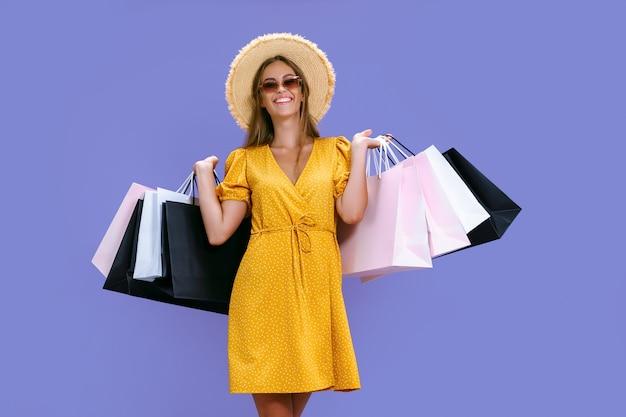 Leuk uitziend meisje draagt kleding terwijl ze kleurrijke pakketten op paarse achtergrond grote verkopen houdt