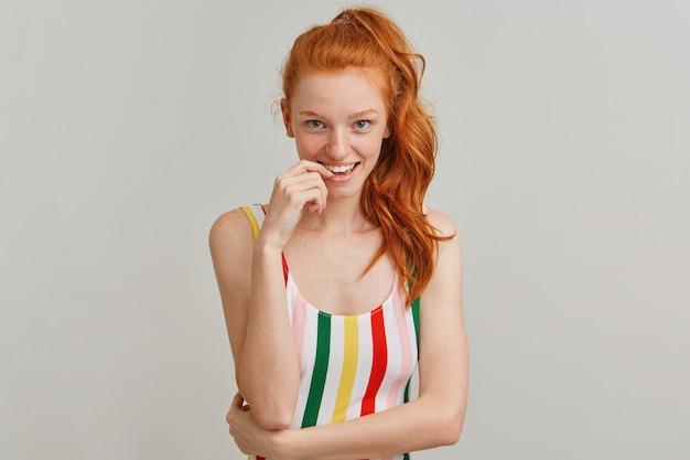 Leuk uitziende vrouw, flirterig roodharig meisje met paardenstaart en sproeten, gestreept kleurrijk zwempak