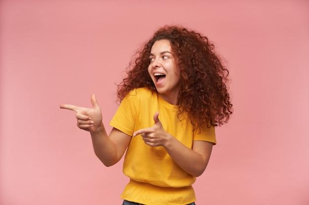 Leuk uitziende vrouw met rood krullend haar, gekleed in een geel t-shirt