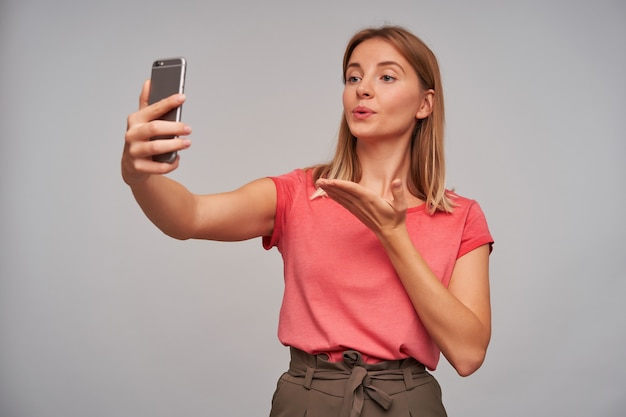 Leuk uitziende vrouw, mooi meisje met blond haar. ik draag een roze t-shirt en een bruine rok. selfie maken, chatten met vriend, luchtkus sturen over grijze muur