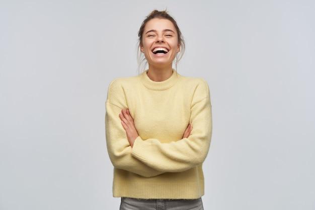 Leuk uitziende vrouw, mooi meisje met blond haar verzameld in een knot. gele trui dragen. lachend met gesloten ogen en gekruiste armen op de borst. tribune geïsoleerd over witte muur
