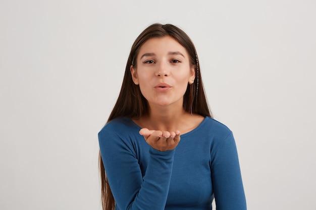 Leuk uitziende vrouw, mooi meisje met donker lang haar, gekleed in een blauwe trui