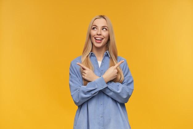 Leuk uitziende vrouw, mooi meisje met lang blond haar. het dragen van een blauw shirt. mensen en emotie concept. kijkend naar links en beide kanten wijzend op kopie ruimte, geïsoleerd op oranje achtergrond
