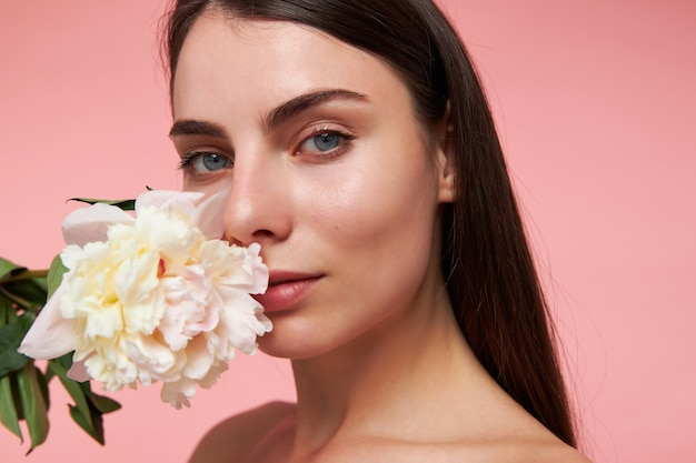 Leuk uitziende vrouw, mooi meisje met lang donkerbruin haar en een gezonde huid, met een bloem naast haar gezicht. kijken, close-up, geïsoleerd over pastel roze muur