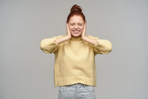Leuk uitziende vrouw, mooi meisje met rood haar verzameld in een knot. pastelkleurige gele trui en spijkerbroek aan. bedek haar oren en loenst. stand geïsoleerd over grijze muur