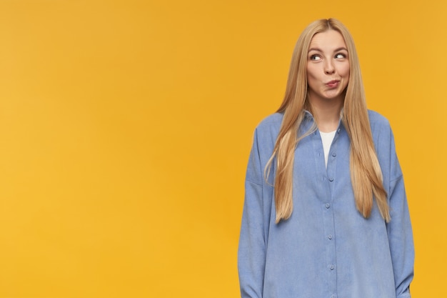Leuk uitziende vrouw, nieuwsgierig meisje met lang blond haar. het dragen van een blauw shirt. emotie concept. beurt lippen, heeft lastige gedachten. kijken naar links op kopie ruimte, geïsoleerd op oranje achtergrond