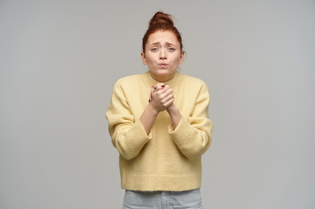Leuk uitziende vrouw, wanhopig meisje met rood haar verzameld in een knot. pastelkleurige gele trui en spijkerbroek aan. houd haar armen bij elkaar, smekend. geïsoleerd over grijze muur