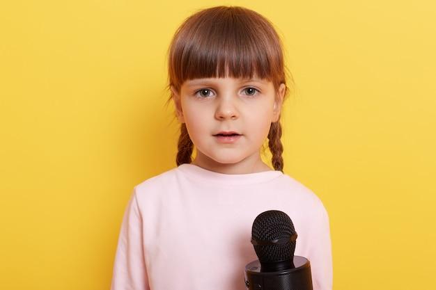 Leuk verlegen kind met lichtroze shirt dat in de microfoon spreekt, met een beetje verwarde blik, klein kind met staartjes dat wordt geïnterviewd tegen een gele muur.