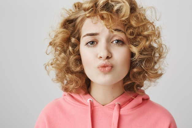 Leuk verlegen krullend meisje die lippen vouwen die proberen te kussen