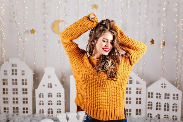 Leuk, verlegen meisje glimlacht bescheiden en poseert met opgeheven armen in gezellig interieur ingericht voor nieuwjaar