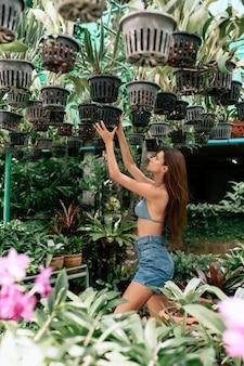 Leuk verleidelijk jong meisje in een sexy bovenkant met blauwe ogen die in een groene tuin met in openlucht hangende groene potten van installaties stellen.
