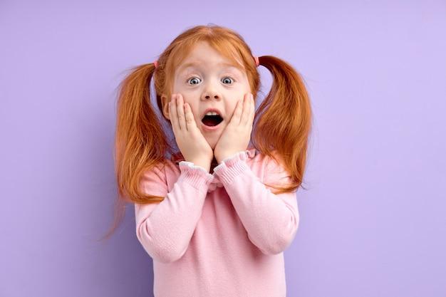 Leuk verrast meisje met gember rood haar en sproeten staat op paarse wangen aan te raken