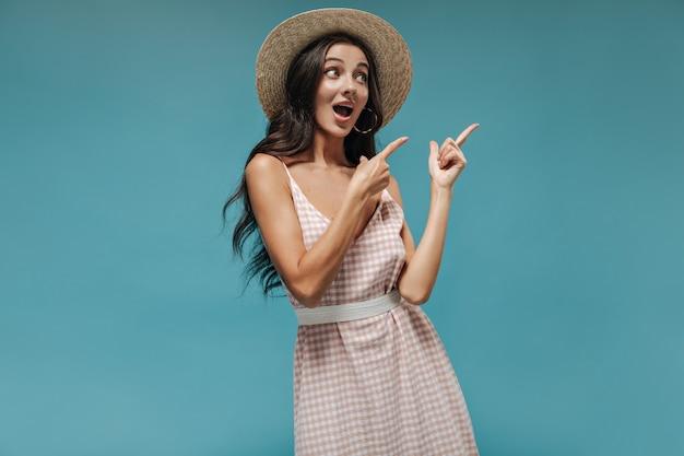 Leuk verrast meisje met lang mooi haar in moderne oorbellen, coole hoed en stijlvolle lichte outfit wijzend naar plaats voor tekst