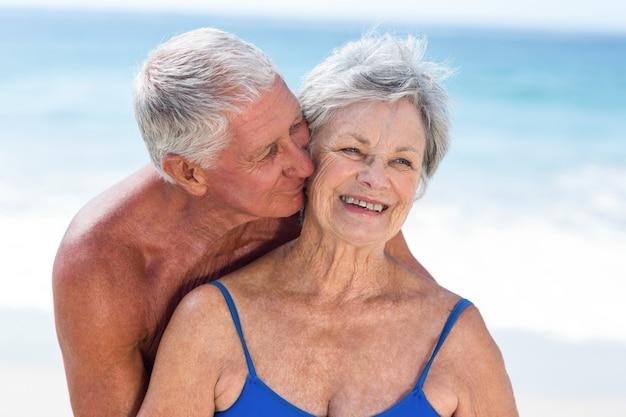 Leuk volwassen paar omarmen op het strand