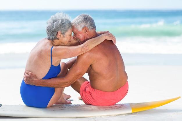 Leuk volwassen paar zittend op een surfplank