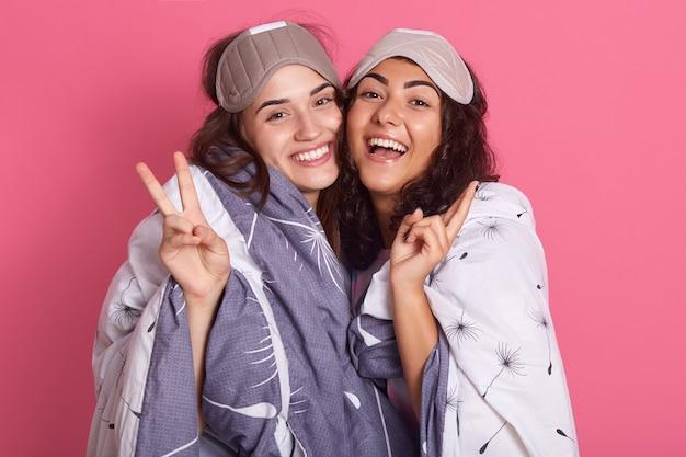 Leuk vriendenmeisje in nachtkostuum voor een pyjamapartij op roze achtergrond