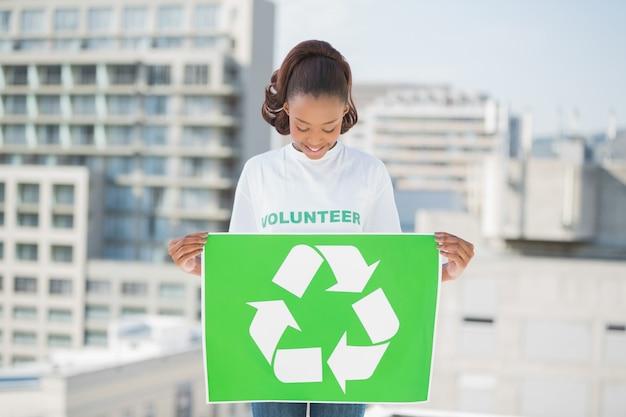 Leuk vrijwilligersvrouw houdend recyclingsteken