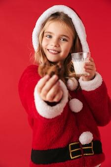 Leuk vrolijk meisje dat geïsoleerde kerstkostuum draagt, melk van een glas drinkt, koekjes eet