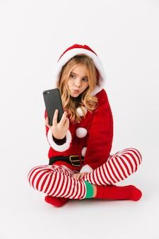 Leuk vrolijk meisje dat geïsoleerde kerstkostuum draagt, mobiele telefoon houdt, een selfie neemt