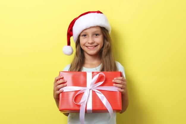 Leuk vrolijk meisje in een kerstmuts op een gekleurde achtergrond met een cadeau