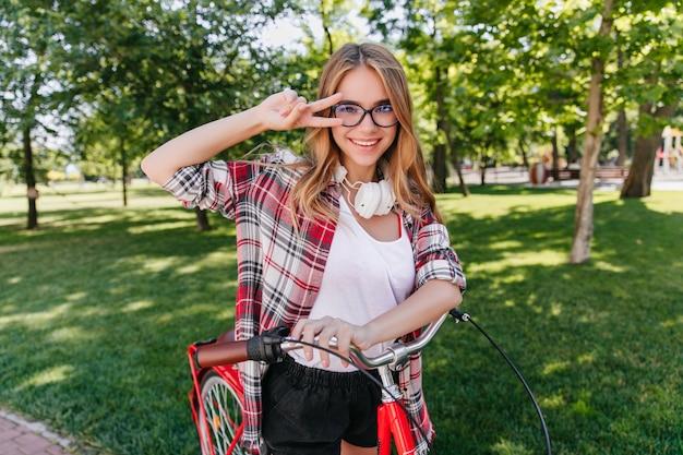 Leuk vrouwelijk model in glazen poseren met vredesteken op aard. aanbiddelijk blondemeisje die op fiets in park berijden.